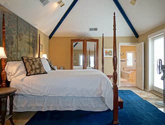 The Asti has an elegant bed and a vaulted ceiling.